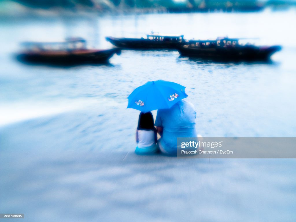 Father And Daughter Sitting With Umbrella On Pier At Lake : Foto stock