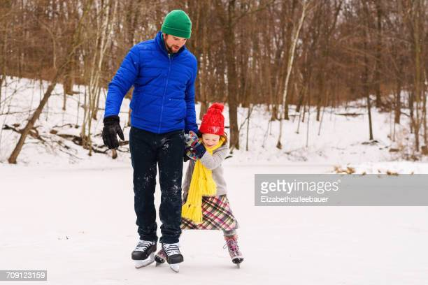 Father and daughter skating on frozen pond
