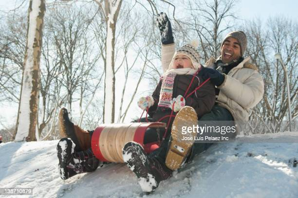 father and daughter sledding down snow covered hill - tobogganing stock pictures, royalty-free photos & images