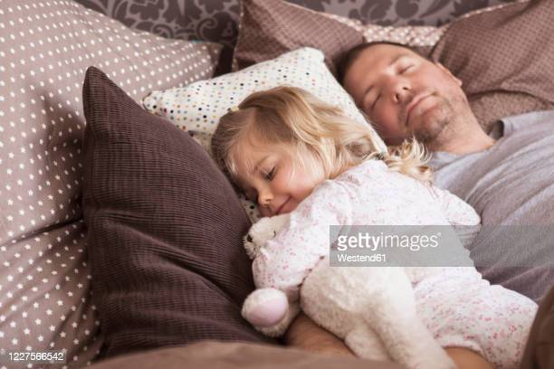 father and daughter sleeping in bed - midday stock pictures, royalty-free photos & images