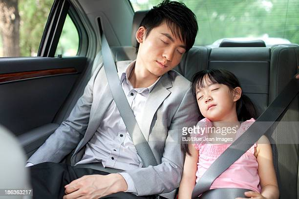 Father and daughter sleeping soundly in car back seat