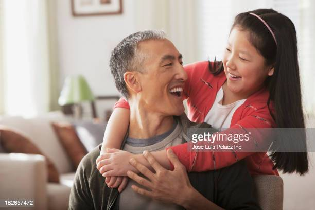Father and daughter smiling in living room