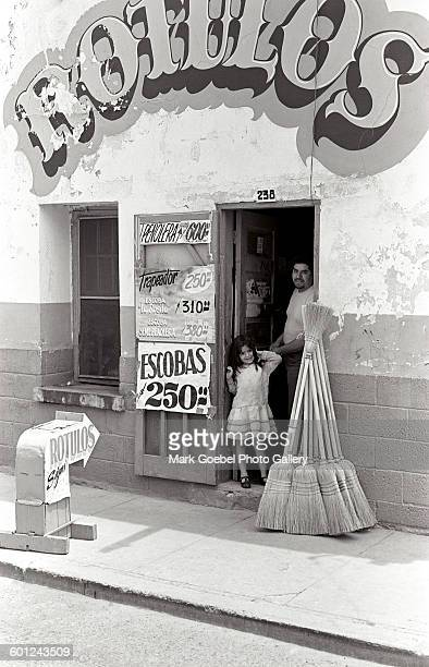 Father and daughter stand in the doorway of a broom vendor business, Juarez, Mexico, late 1980s.