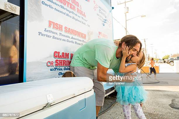 Father and daughter standing beside fast food trailer, daughter kissing father