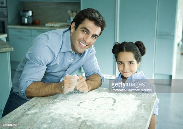 Father and daughter standing by counter with flour sprinkled on it, heart drawn in flour