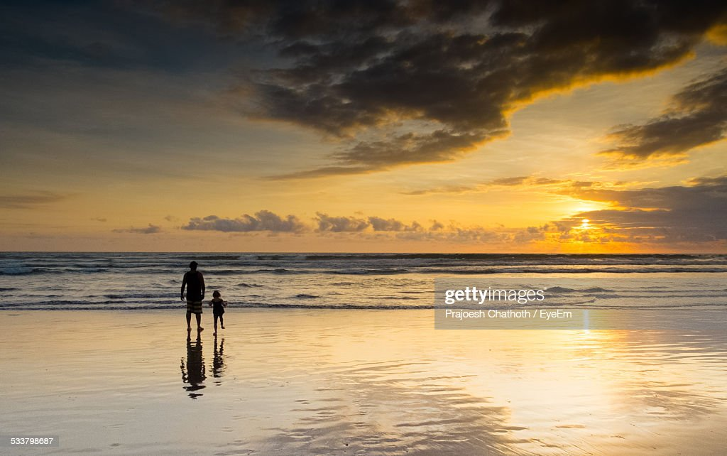 Father And Daughter Standing On Beach During Sunset : Foto stock