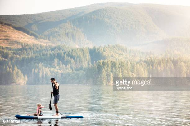 father and daughter standup paddleboarding - noroeste do pacífico imagens e fotografias de stock