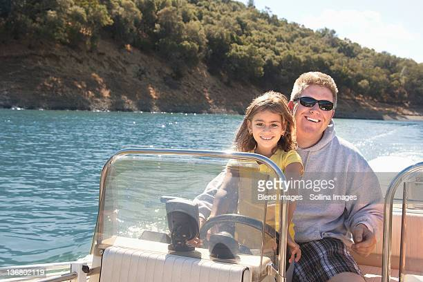 Father and daughter steering boat on lake