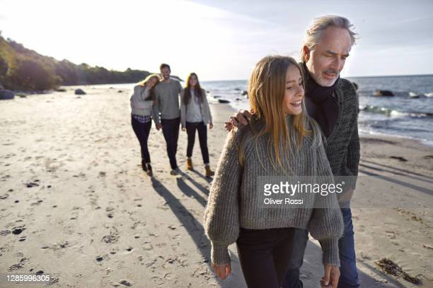 father and daughter strolling on the beach with family in background - vijf personen stockfoto's en -beelden