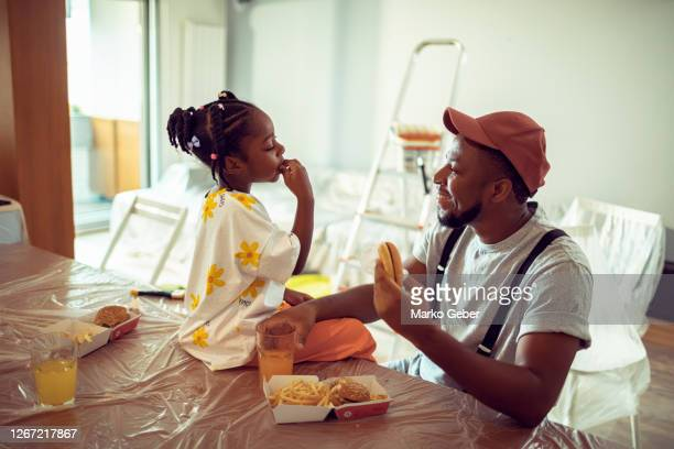 father and daughter taking a break from painting - daughter stock pictures, royalty-free photos & images