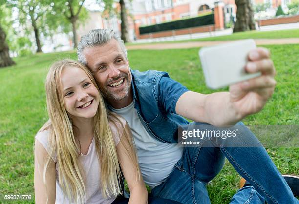 Father and daughter taking a selfie at the park