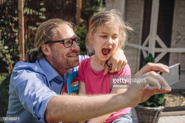 Father and daughter taking a selfie in garden