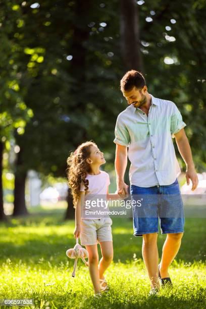 Vater und Tochter spazieren, Hand in Hand