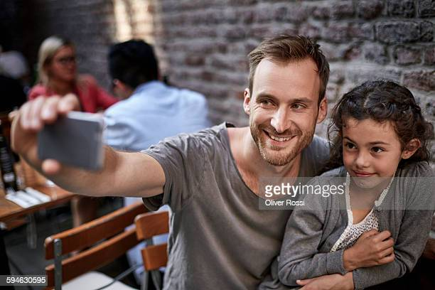 Father and daughter taking selfie in a restaurant