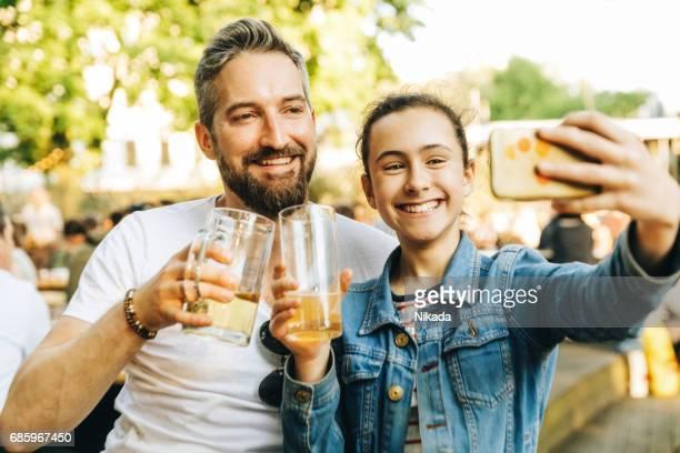 Vater und Tochter nehmen Selfie im Biergarten