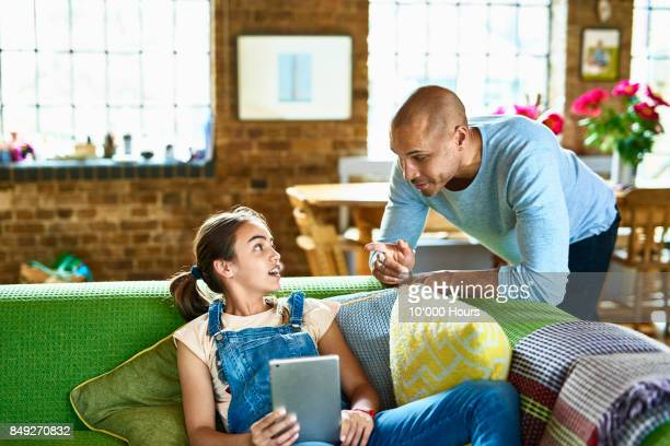 Father and daughter talking in livingroom