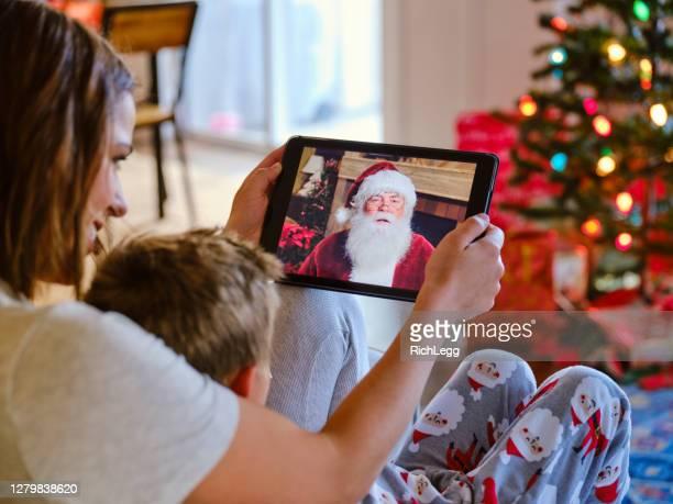 vater und tochter im gespräch mit dem weihnachtsmann auf einem video-anruf - mother daughter webcam stock-fotos und bilder