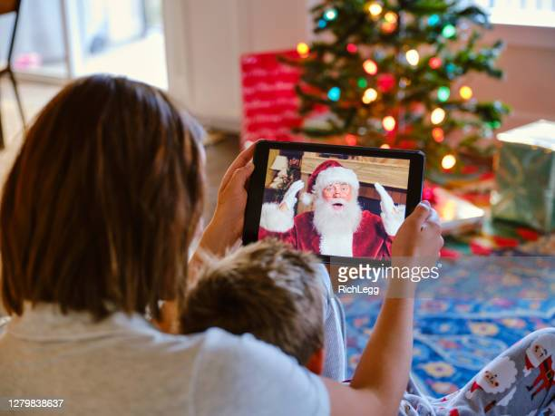 father and daughter talking to santa claus on a video call - father christmas stock pictures, royalty-free photos & images