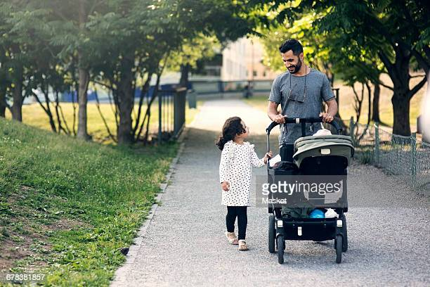 Father and daughter talking while walking with baby stroller on footpath at park
