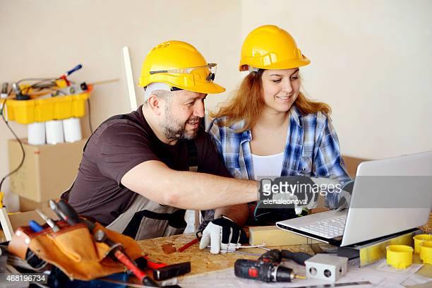father and daughter teen in working clothes in a construction workshop