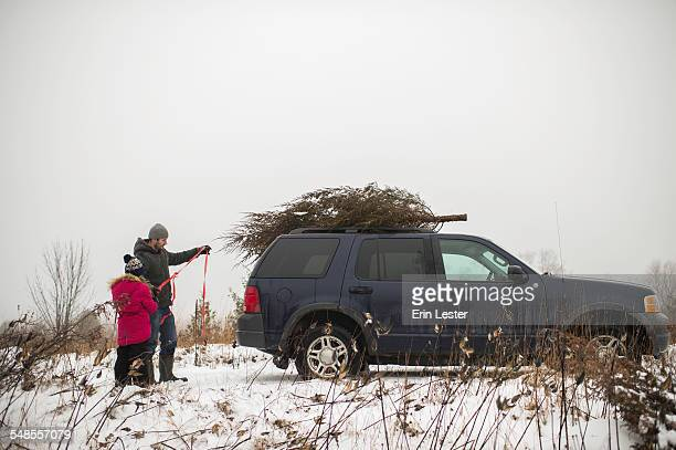 Father and daughter tying christmas tree on roof of car