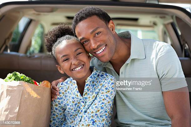 father and daughter unloading groceries from car - single father stock pictures, royalty-free photos & images