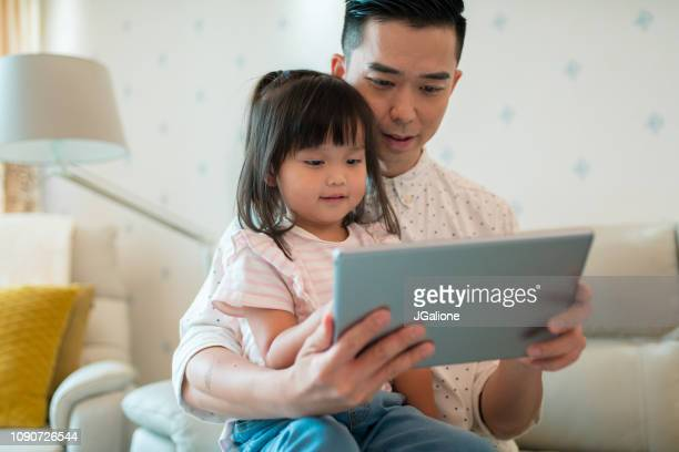 Father and daughter using a digital tablet