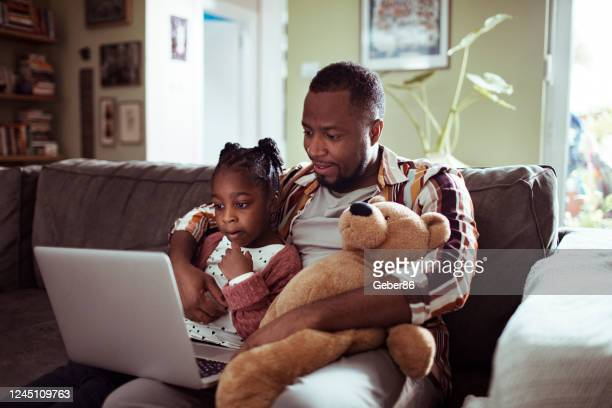 father and daughter using a laptop - teddy bear stock pictures, royalty-free photos & images