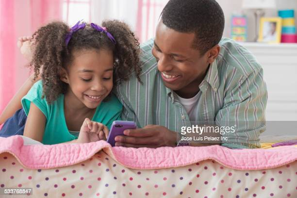 Father and daughter using cell phone together on bed