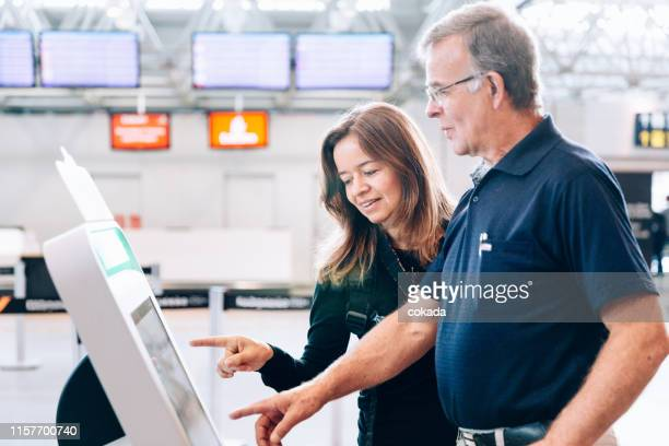 father and daughter using check in totem at the airport - totem pole stock pictures, royalty-free photos & images