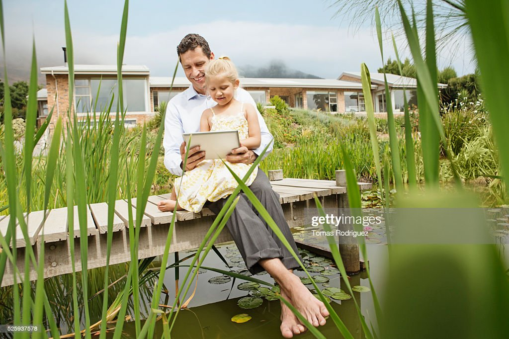Father and daughter using digital tablet (4-5) outdoors : Foto stock