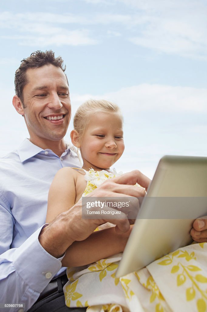 Father and daughter using digital tablet (4-5) outdoors : Stock Photo