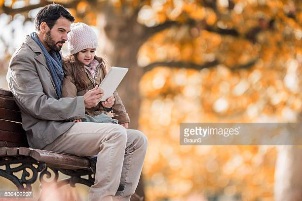 Father and daughter using digital tablet outdoors.