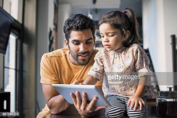 father and daughter using digital tablet - one parent stock pictures, royalty-free photos & images