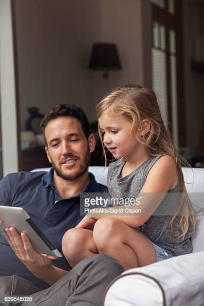 Father and daughter using digital tablet together