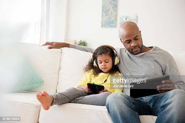 father and daughter using digital tablets on sofa - upload stock pictures, royalty-free photos & images
