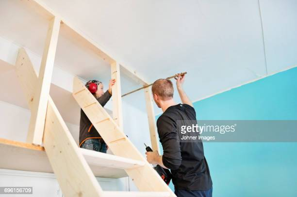Father and daughter using drill at home