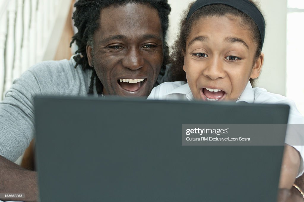 Father and daughter using laptop : Stock Photo