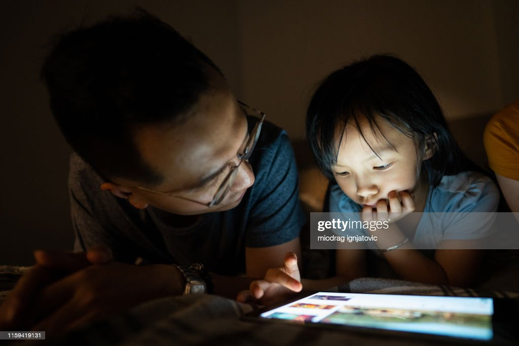 Father and daughter using tablet before sleeping : Stock Photo