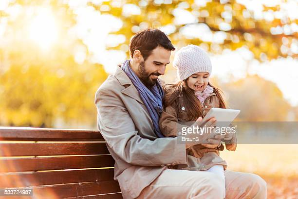 Father and daughter using touchpad outdoors.