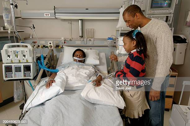 father and daughter (8-10) visiting mature female patient in hospital - patient on ventilator stock pictures, royalty-free photos & images
