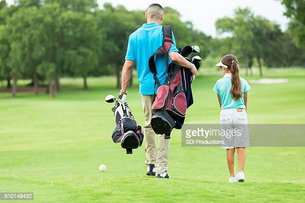 Father and daughter walk on golf course