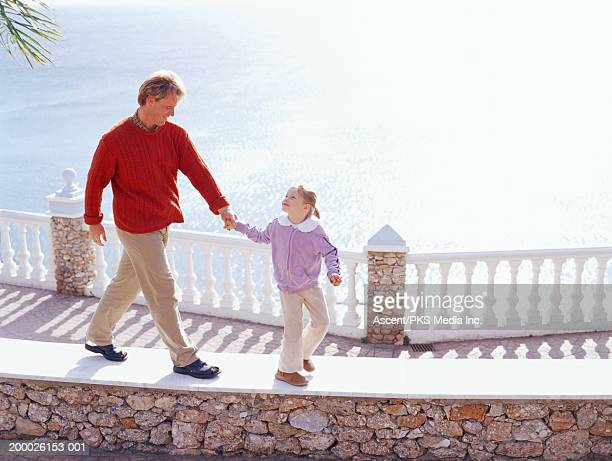father and daughter (6-8)walking along raised walkway, overhead view - シングルファザー ストックフォトと画像