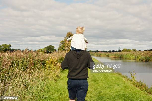 father and daughter walking along the canal together - paternity leave stock pictures, royalty-free photos & images