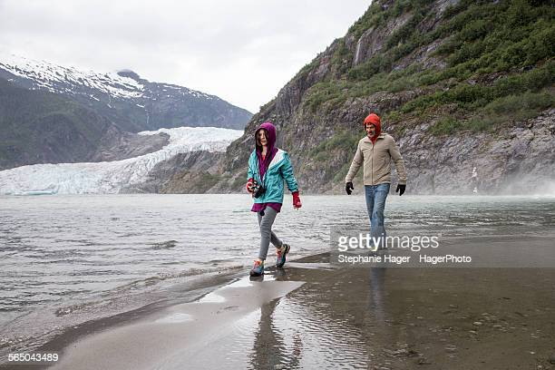Father and daughter walking by glacier