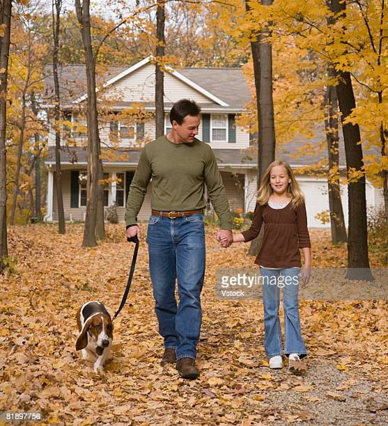 Father and daughter walking dog in woods