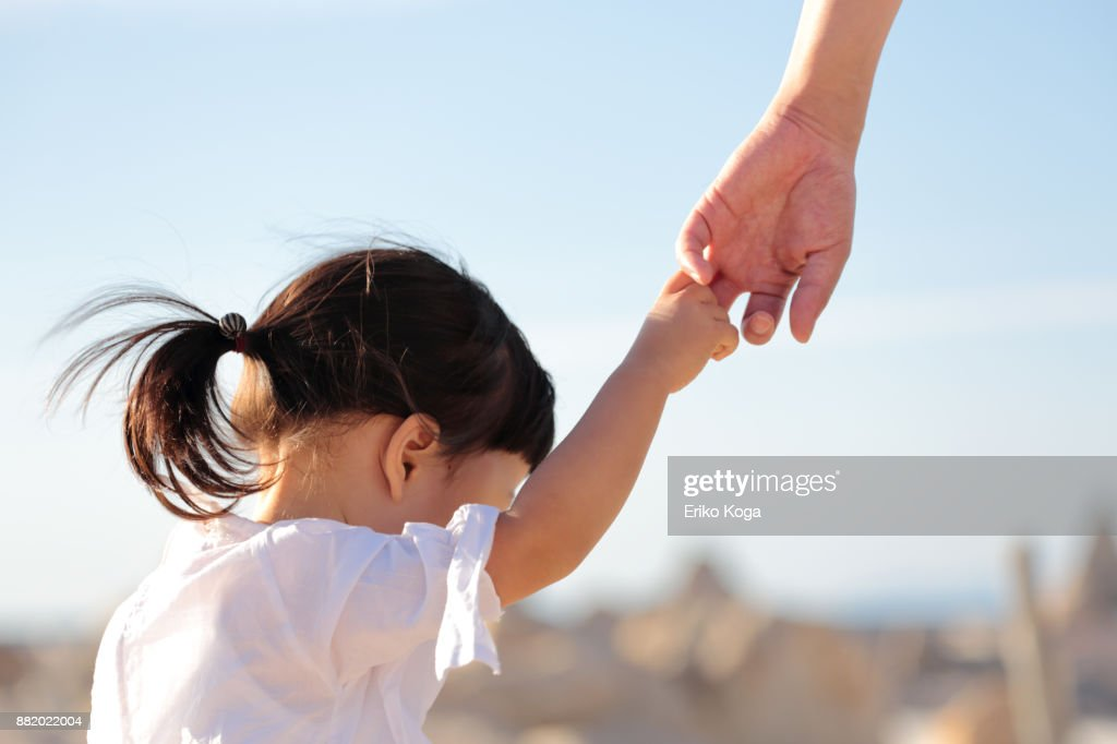 Father and daughter walking hand in hand on beach : Stock Photo
