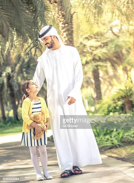 Padre e hija caminando en un parque