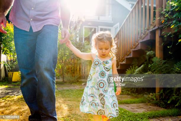 Father and daughter walking in backyard