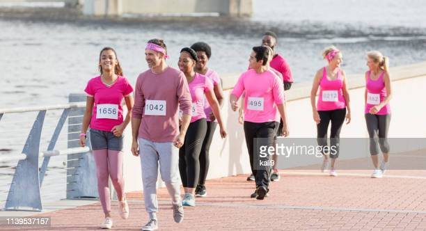 father and daughter walking in breast cancer race - charity benefit stock pictures, royalty-free photos & images